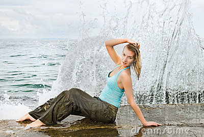Wet girl sitting near the ocean