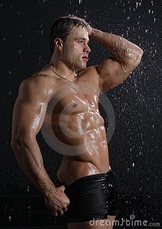 Wet muscle sexy young man posing under the rain