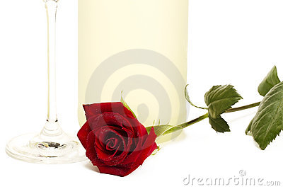 Wet red rose in front of a prosecco bottle and a c