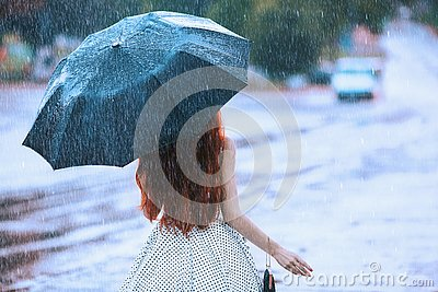 Wet weather. Autumn rain. Lonely girl in polka dots dress hold black umbrella. Raining in city. Wet umbrella against the backdrop Stock Photo