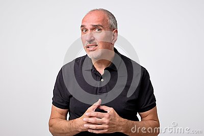 What did you say, repeat concept. Portrait of annoyed questioned attractive mature man in black shirt Stock Photo