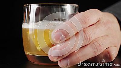 Whiskey Sour cocktail A mão toma o coquetel acabado, que é feito de uísque misto, xarope de açúcar, sumo de limão, esplas de ovo filme
