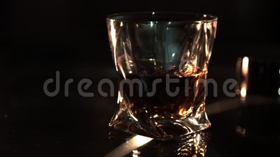 Whisky in a glass on glass table and dark background, selective focus. stock footage