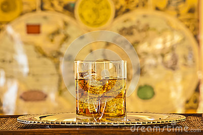 Whisky glass on silver platter on wooden table