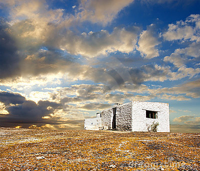 White abandoned house under dramatic sunset skies