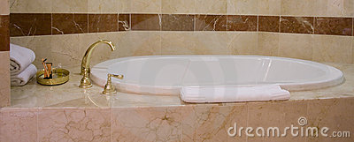 White bathtub and brass taps