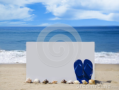 White board with flip-flops on sandy beach