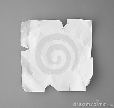 White broken and creased paper note  on a gray backgroun