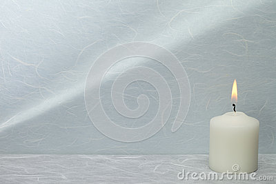 White candle with background reflection