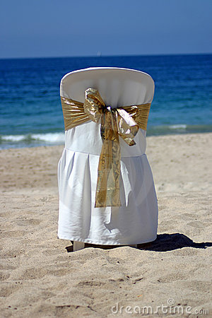 White chair with gold ribbon for a beach wedding