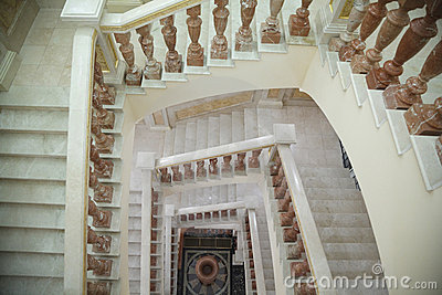 White circular marble staircase with brown stand