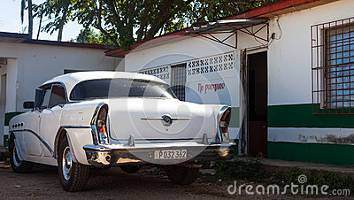 A white classic car parked front of house