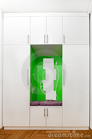 White closet with mirrors and green decoration