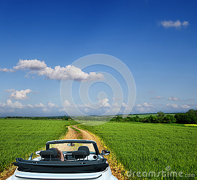 White convertible on a country road through fields