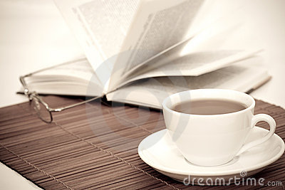 White cup of coffee and book with glasses