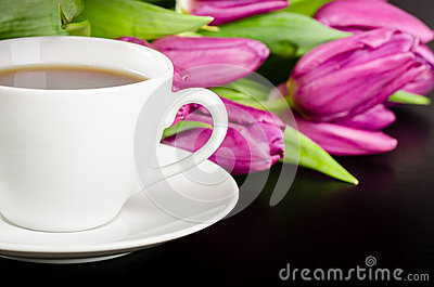 White cup of coffee with bunch of purple tulips on dark backgrou
