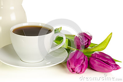 White cup of coffee with bunch of purple tulips on white backgro