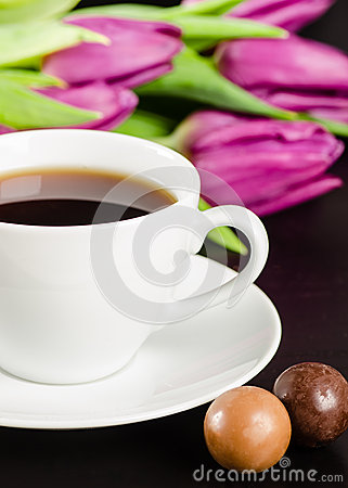 White cup of coffee with candies and purple tulips