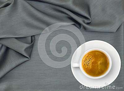 White cup of coffee over grey cloth
