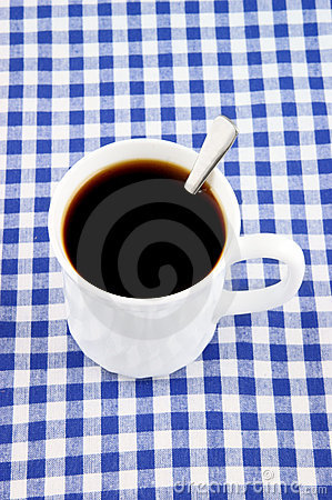 White cup of coffee with teaspoon