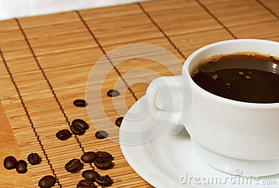 White cup of coffee on a wicker table cloth
