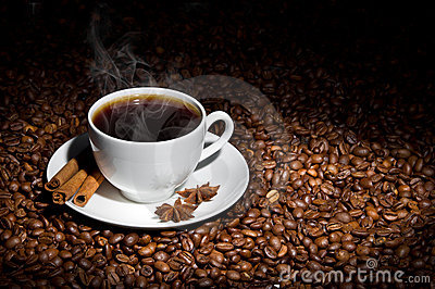 White cup of hot coffee on coffee beans