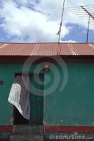 White Curtain Blows from Door of Green House with Antenna