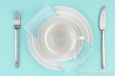 White dishes on aqua tablecloth