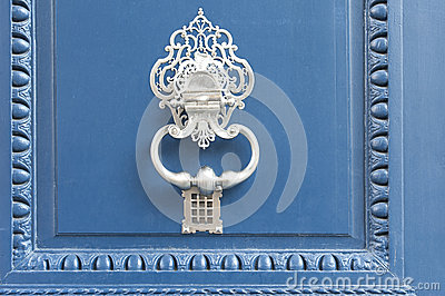 White doorknocker on a blue door
