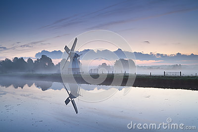 White Dutch windmill by river in misty sunrise