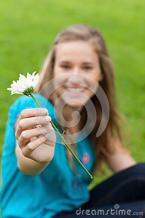 White flower held by a young smiling woman