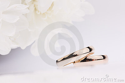 White flowers and  wedding rings