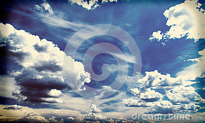 White fluffy clouds over blue sky, filtered image instagram effect.