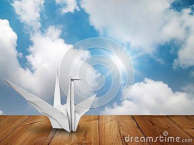 White fold paper bird on wood floor