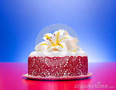 White fondant cake decorated with red lace and edible candy lily