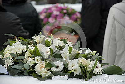White Funeral flowers in the snow before a caket