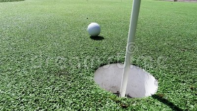 White golf ball hitting flag stick and falling into hole on putting green. Golf ball and flag stick on artificial turf practice putting green - competition and stock footage