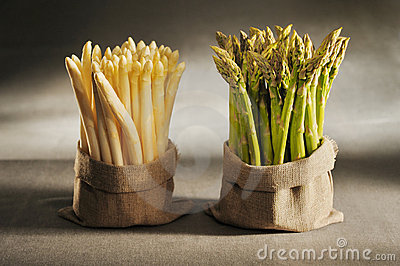 White and green asparagus in cloth bags