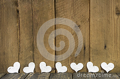 White hearts on a wooden old rustic background.
