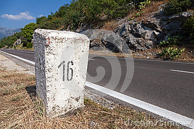 White kilometer stone post on the roadside