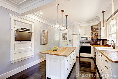 White kitchen with wooden counter top island and TV