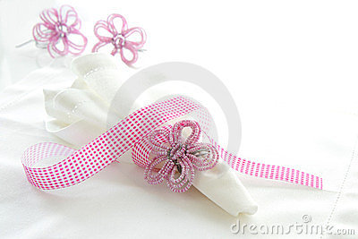 White linen serviette with pink beaded napkin ring