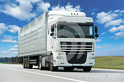 White lorry with grey trailer over blue sky