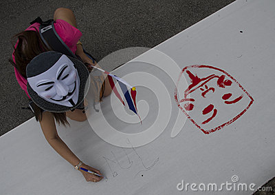 WHite mask protestor holding Thai flag paints on banner Editorial Photography
