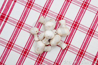 White mushrooms on a red tablecloth