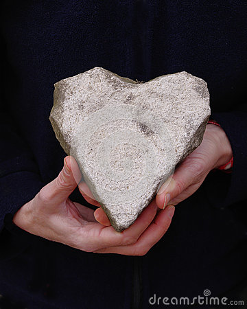 White natural stone heart in hands