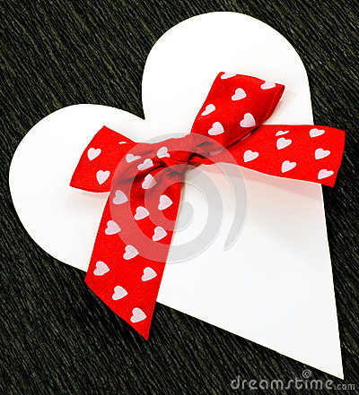 White paper heart with red ribbon bow