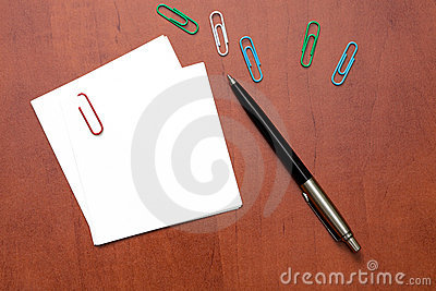 White paper note with a clip and pen