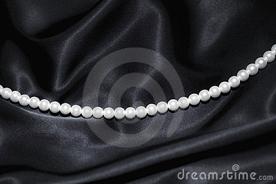 White pearl necklace on black silk