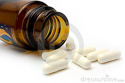 White pills and brown prescription bottle